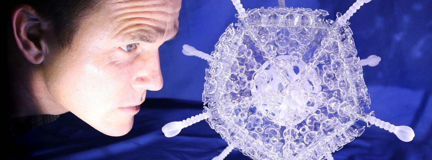 Luke Jerram with his COVID-19 vaccine glass sculpture