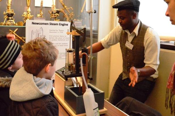 Objects of Invention: student engineer giving a demonstration of a model Newcomen steam pump
