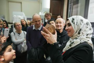 Muslim woman wearing patterned hijab (Islamic headscarf) giving a tour of the Museum, she is holding up a paper astrolabe to the audience.